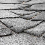 Old composite shingles roof with damage Houston