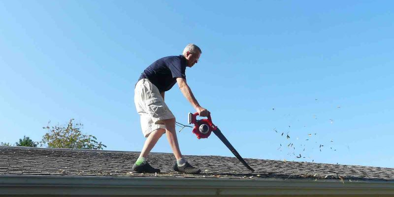 Using a blower to remove leaves from a Houston roof.