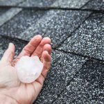 Hail in hand on a rooftop after hail storm. Houston roofing company for roof repair.