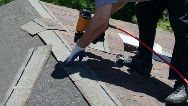 roofer installing new shingles on a roof