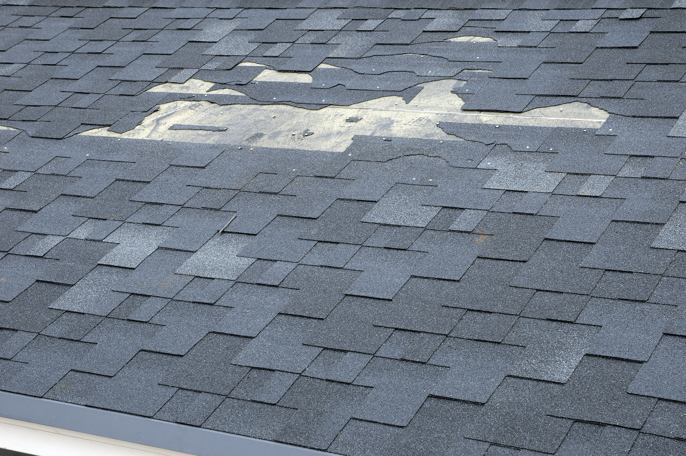 roof with severe shingle damage and missing shingles