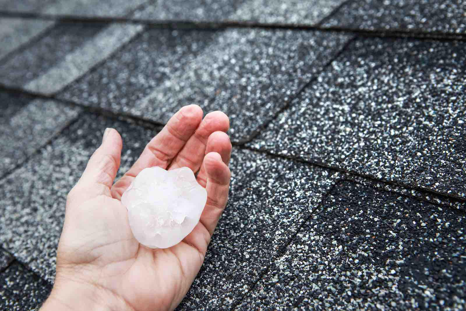 Hand holding hail the size of a gold ball after it damages Spring, Texas roofing