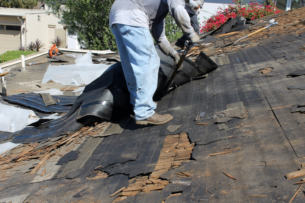 Houston roofer tearing down old roof damage and completing Spring, TX roof replacement before a hurricane hits