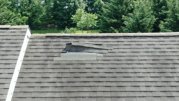 Torn roof shingles due to Cypress roof wind damage