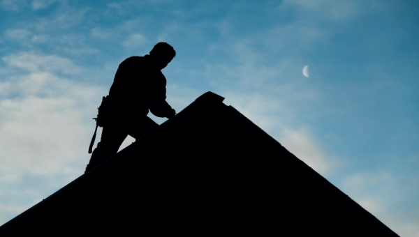 Silhouette of Houston roofer completing Cypress roof repairs for the holidays