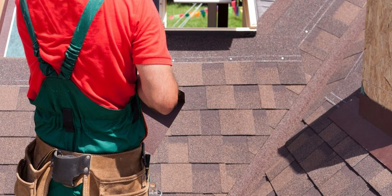 Roofer working on roof. Roof inspection. Shingles